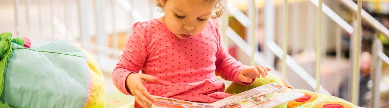 Ein kleines Mädchen schaut ein Buch an